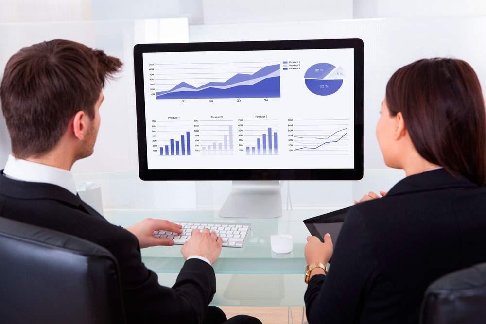 empresarios observan software de ventas en monitor