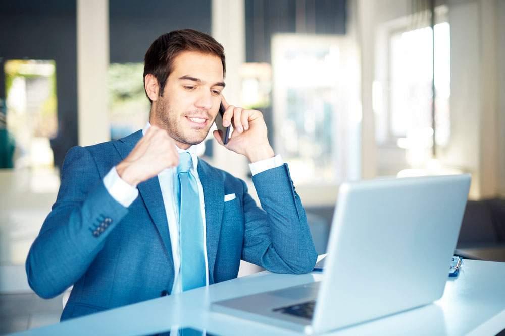 Joven empresario celebrando su éxito de ventas
